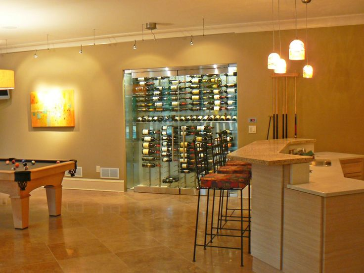 This stylish basement game room features a modern glass wine cellar accentuated by industrial track and pendant lighting.