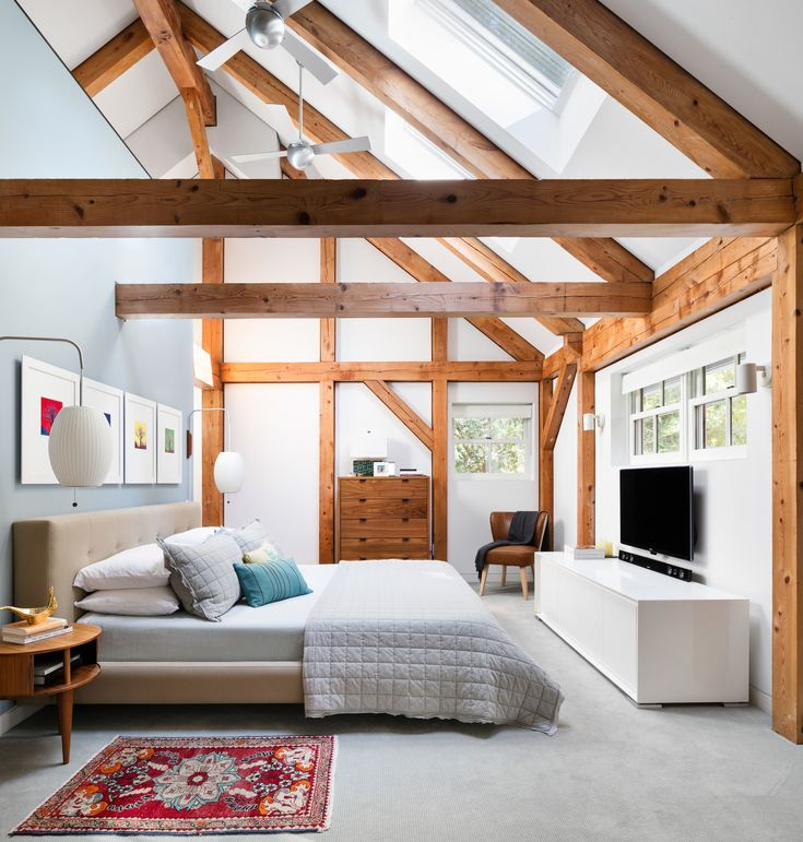 Once covered in dark pine, a New York home is now radiant in Paper White by Benjamin Moore. The bed, flanked by George Nelson sconces, is from Crate and Barrel.
