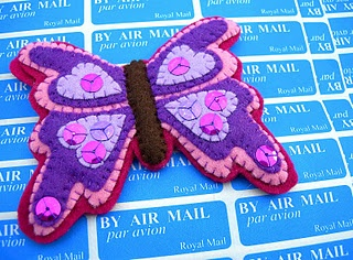 Pretty felt butterfly decorated in colorful layers & sequins.