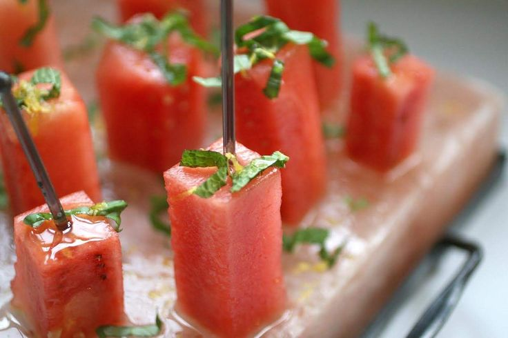 Watermelon cubes are served on a pink Himalayan salt plate with fresh herbs and a mixture of olive oil and honey.
