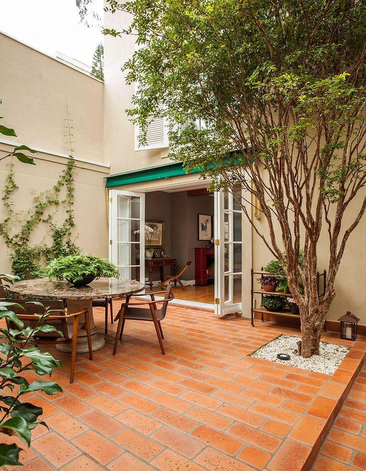 Decoração de casa com móveis antigos e contemporâneos. Na varanda mesa de jantar redonda e plantas.