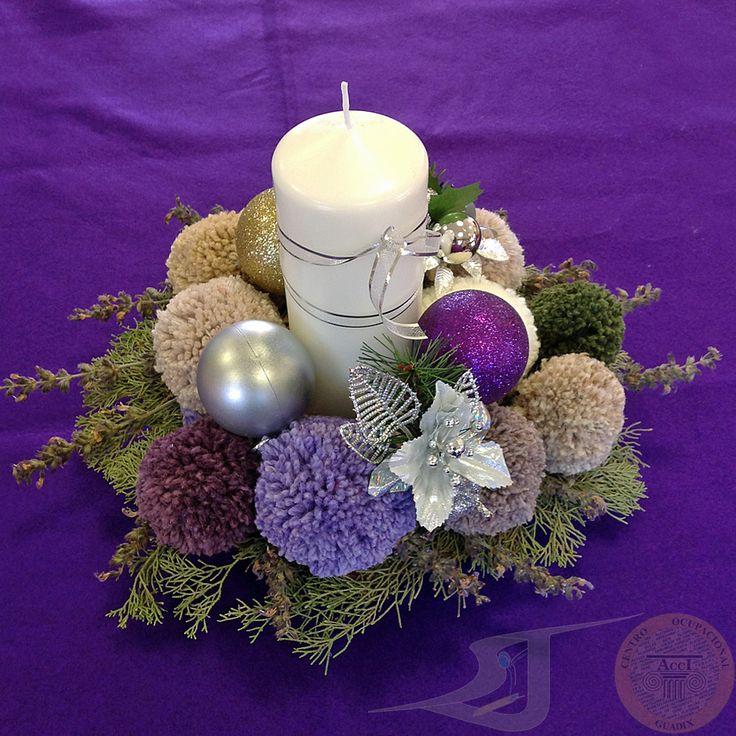 Centro de Mesa realizado con pompones de lana, plantas aromáticas, bolas de navidad, y una vela central de color blanco decorada con un lazo plateado.