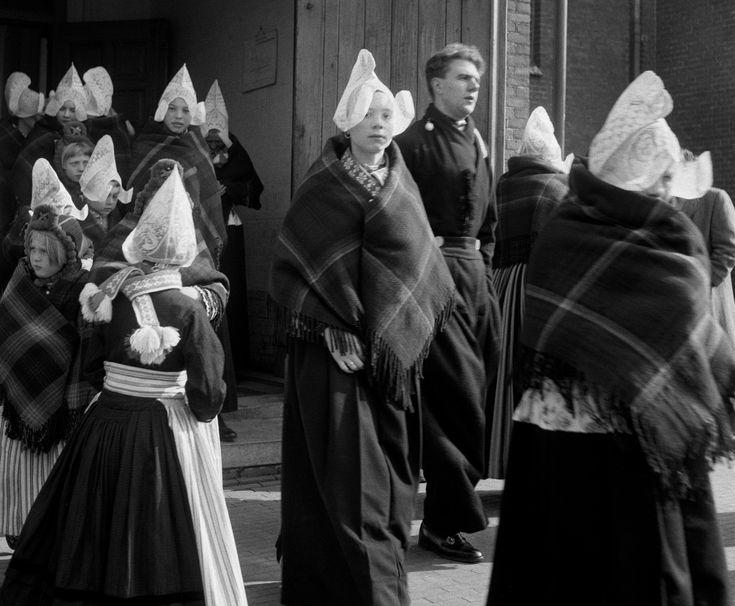 Volendammers in klederdracht verlaten de kerk (1950-1960) fotograaf: Oorthuys, Cas #NoordHolland #Volendam