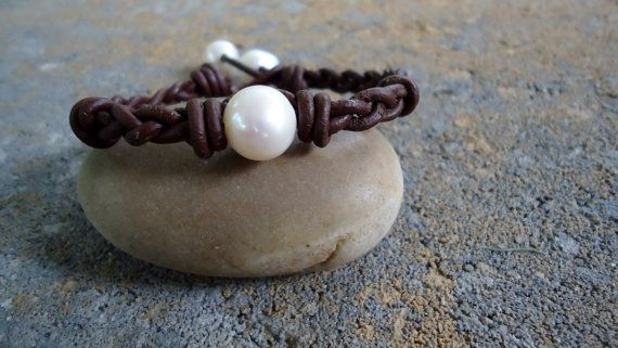 Earthy and chic !    A lustrous 11-12 mm white freshwater pearl is braided and knotted on multiple strands of rich dark brown knotted leather . Two