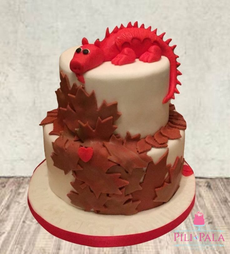 Wales/Canada themed gluten free anniversary cake. Cascading hand cut maple leaves, topped with a Welsh dragon