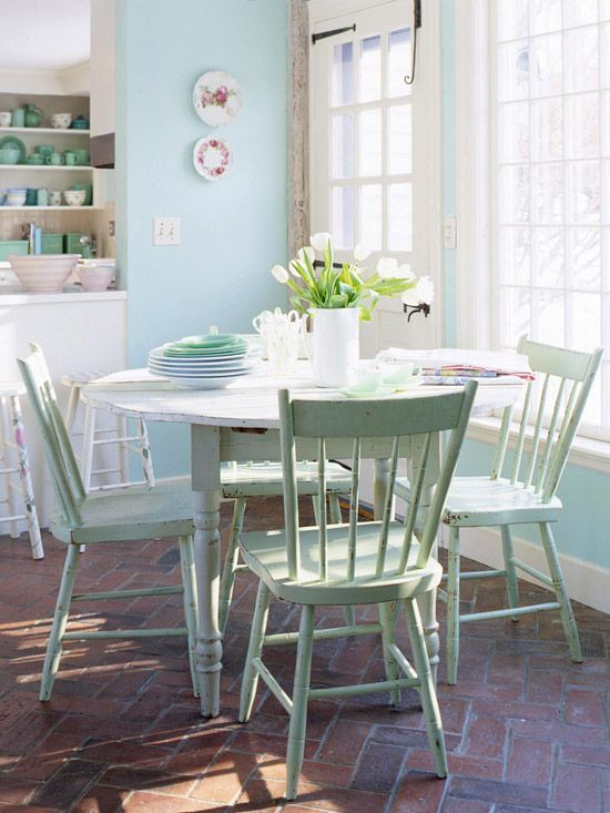 Family Space In-kitchen nooks are great for casual family meals because the food can go from kitchen to table in seconds. Here, a white table and green chairs create a cottage-chic space for mealtime. Kitchen dishware that matches the seafoam green chairs unifies the two areas.