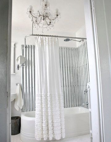 Love this! Corrugated Metal surrounding bathtub.For the remodel from Country Living, the galvanized sheets were cut to fit and then finished with Rust-Oleum Crystal Clear Enamel before screwing them in place. Self-sealing roofing screws and metallic caulk were used to prevent leaks. Ideally an assembly of a waterproof membrane and pressure treated nailing strips with self sealing washer head screws would work.