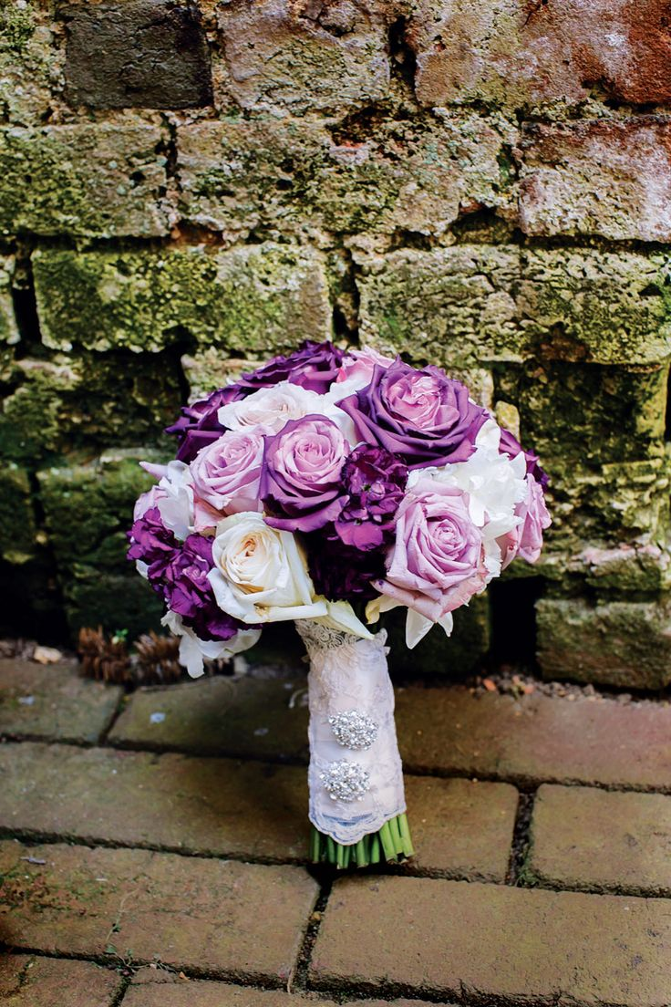 The bride's bouquet of purple and ivory roses is wrapped with lace from her mother's wedding gown