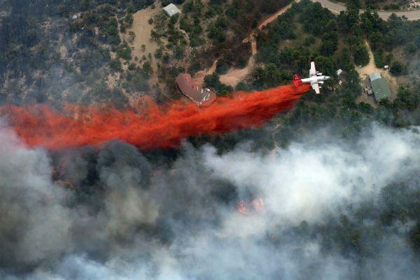 Un avión lanza una línea de retardante de fuego entre las llamas y unas casas en el Bosque Netro en Colorado, Estados Unidos. (AP)