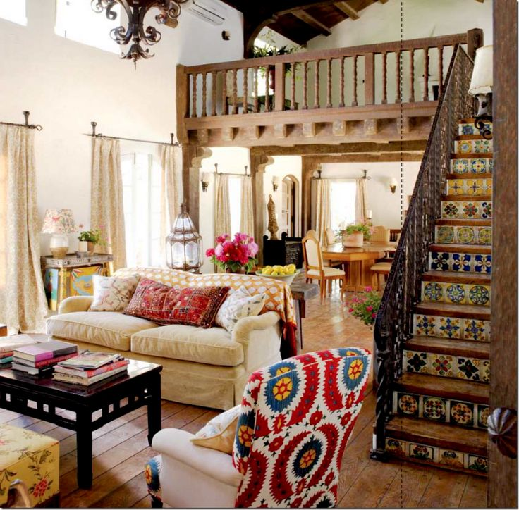 Another view of the antique painted table in Kathryn Ireland's Ojai ranch living room. Note the colorful throw and pillows on the sofa, and the tile stair risers, which are original to the house.