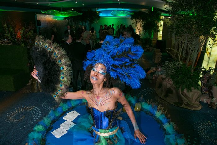 """Allie Awards: Dressed like a fantastical peacock, a strolling performer doubled as a """"living table"""" at the Allie Awards in Atlanta in March. Events of a Lifetime donated the table."""