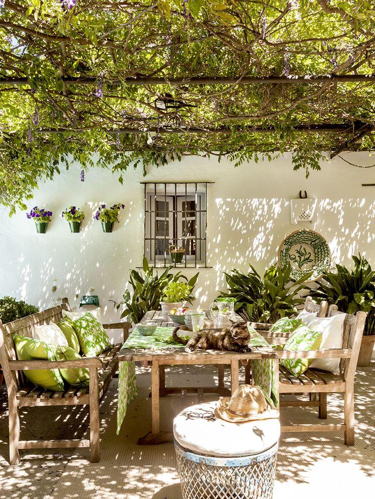 Zona de estar en el porche con pérgola y sillas y mesas de madera