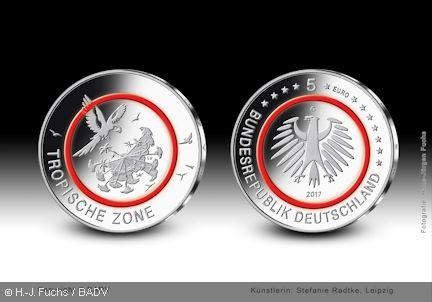 """Die Bundesregierung lässt eine 5-Euro-Sammlermünze """"Tropische Zone"""" mit einem roten Kunststoffring prägen, die am 27. April 2017 ausgegeben wird. Die Münze bildet den Auftakt einer fünfteiligen Serie """"Klimazonen der Erde"""" (2017 - 2021)."""