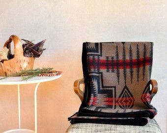 Cette couverture est chaud, moelleux, épais et beau! Il est fait de véritable Pendleton® laine vierge tissu de couverture (ultra-doux et très épais) dans un design classique de bandes et natif se croise en lumière bleue marine, noire, rouge et chinée marron. Cette couverture est une pièce indémodable, de qualité qui va durer et vous réchauffer pour les années à venir. Nous avons relié le bord avec un coordination du Velours milleraies bleu.  Mesures: (167,5 cm) 66 x 73 (185,5 cm)  Pour…
