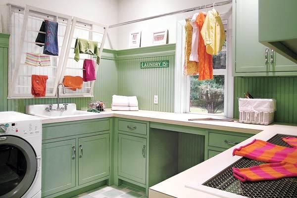 This high-functioning laundry room is decked out in vintage green paint to unify the custom cupboards below and the beadboard above. | Photo: Peter Peter Rymwid