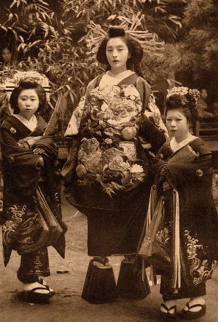 "This is an Oiran, or ""courtesan"". She was actually a high ranking prostitute who  cost more than other prostitutes. Notice her tall shoes! The young girls with her were sold by their families and are being trained in the art from a young age. Also, do not confuse Oiran with Geisha. A Geisha would go ballistic if that happened. Ca. 1905 - 1920."