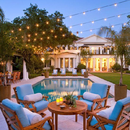 The strung lights look amazing and the pool is so clean looking. Love the palm trees in planters and the teak wood furniture.