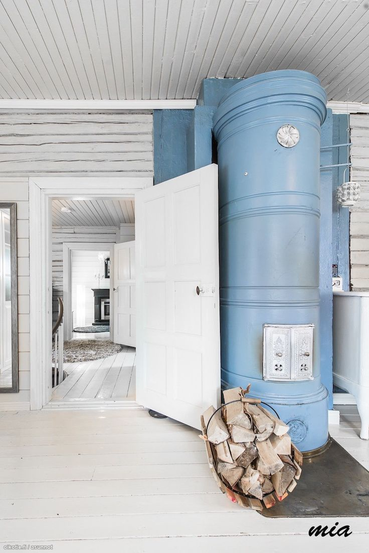 Log walls painted in white and a blue Scandinavian fireplace