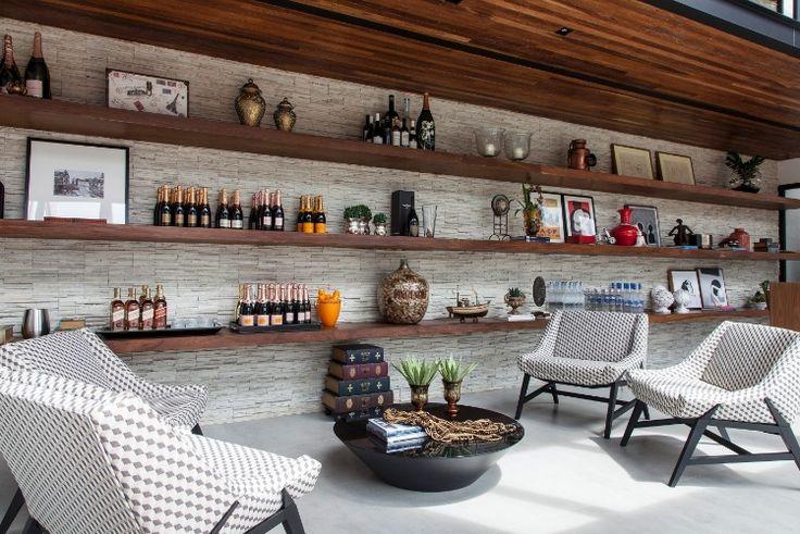 +Sidney+Quintela+do+SQ++Arquitetos+Associados+criou+a+área+de+bar+para+a+casa+em+Salvador+(BA).+As+largas+prateleiras+de+cumaru+foram+instaladas+na+parede+revestida+em+canjiquinha+para+que+uma+parte+da+coleção+de+bebidas+ficasse+em+exibição,+além+de+objetos+decorativos