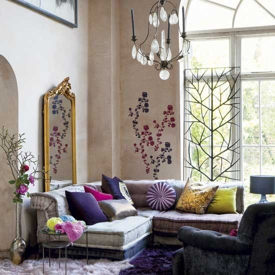 Boho room with neutral walls, couch and gold mirror