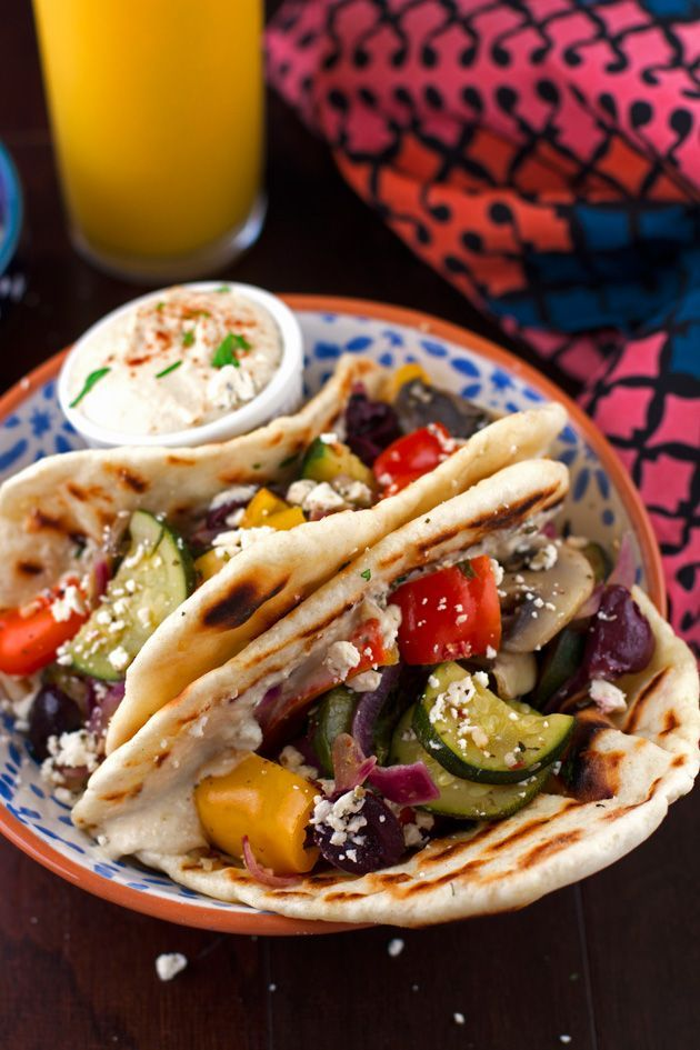 A hummus and sauteed vegetable flatbread wrap that is stuffed with homemade hummus, sauteed zucchini, sweet peppers, red onions, and kalamata olives.