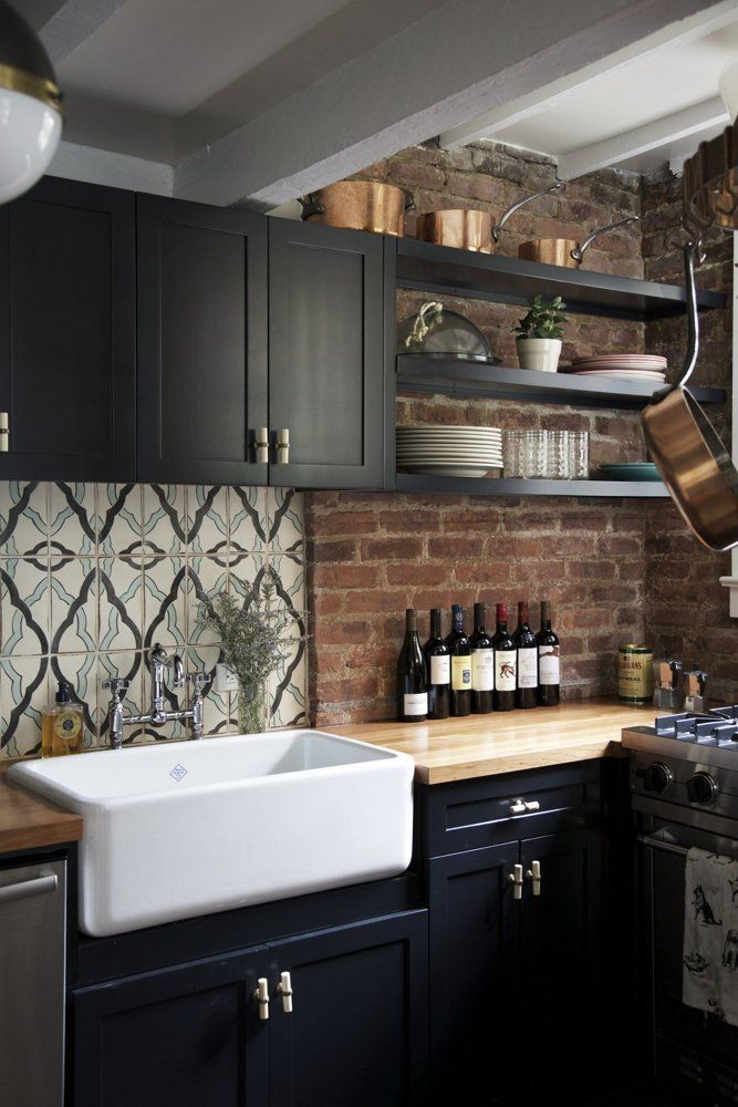 Black kitchen cabinets, brick wall and useful decor of copper-tone cookware and wine bottles.