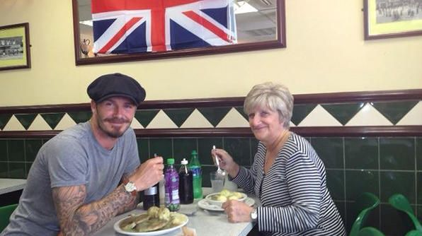 """David Beckham and his mother enjoy bangers and mash in London's East End. Beckham says, """"Here's an insider's tip for a real East London food experience. You've got to try Pie & Mash. Tony Lane's Pie & Mash shop in Waltham Abbey is a favorite."""" - David Beckham"""