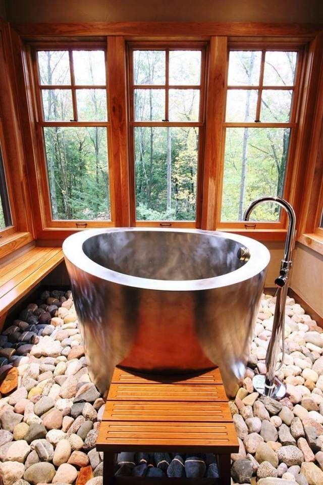 une baignoire ovale sur un tapis de pierres naturelles dans le chalet de montagne