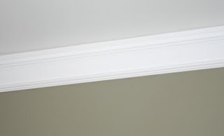 faux crown molding -- baseboard mounted upside down.  Would add a thinner piece below with matching paint in between to make it look even thicker.  My ceilings are so high, no one would know.  ;)