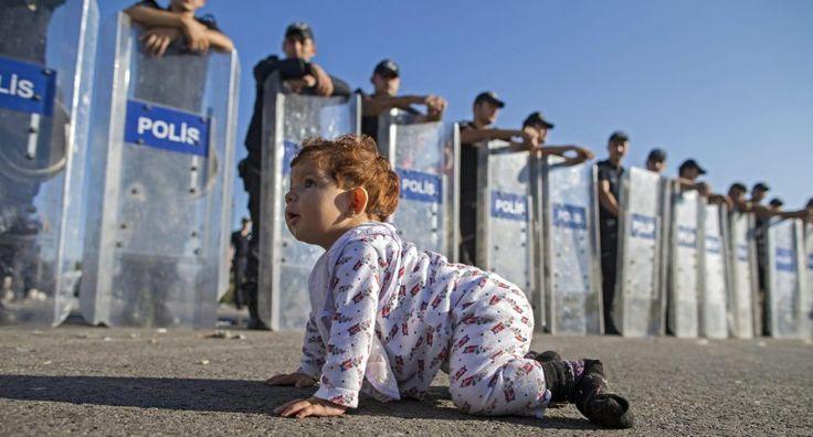Migránsok, gyerek mászik közel a rendőrségnek, a pajzsok Törökországban