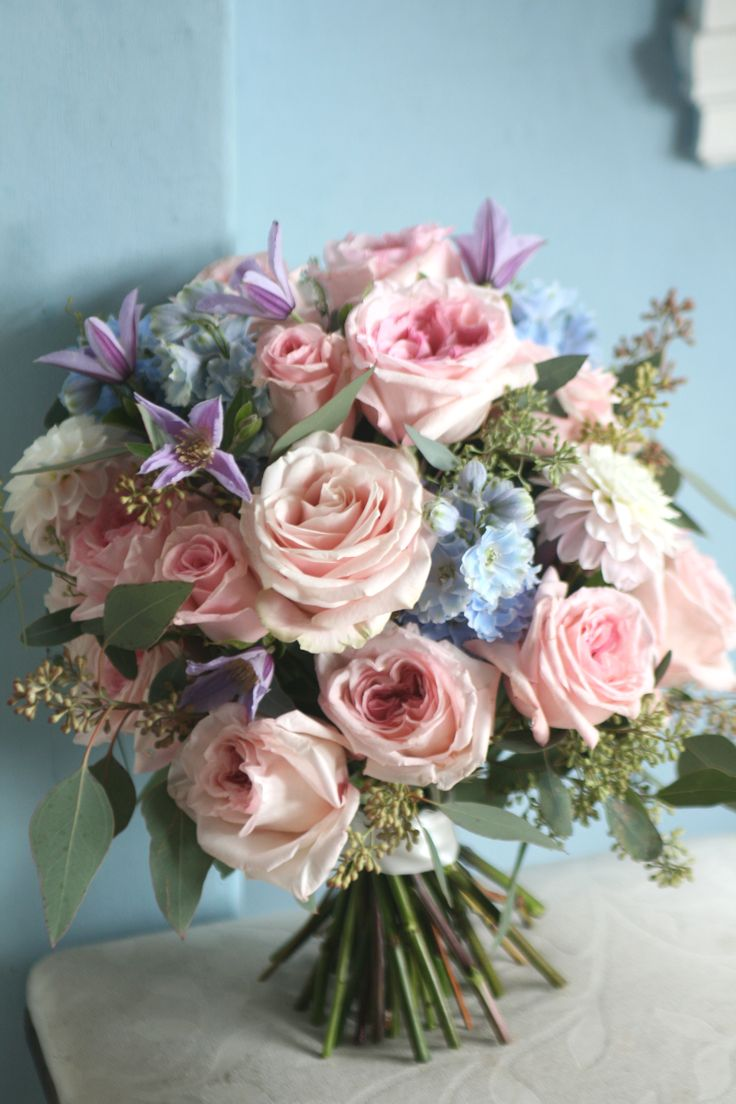 Wedding bouquet in pastel shades with ohara roses, sweet avalanche roses, delphinium, dahlia, clematis and eucalyptus.  Liberty Blooms