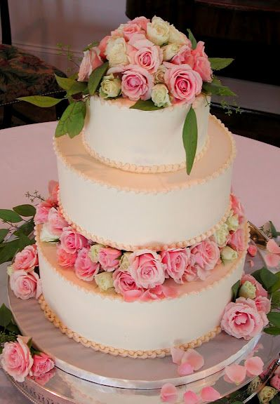 three tiers of sweet frosted cake with a floral spacer & topper. magpies bakery, knoxville tn