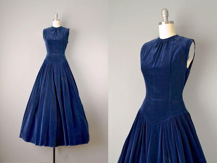 Blauw fluweel perfectie! Dit fluweel mouwloos katoenen jurk uit de jaren 1950-kenmerken een verzamelde hals die leidt tot een op maat gemaakte bodice, eindigend in een v-panel op de heupen. Dit leidt tot meer verzamelen op de heupen die golven in een practisch volledige rok. Knoppen aan de achterkant die gaan vanaf de bovenkant van de hals tot onder de taille gedekt — een totaal van 26 knoppen. Perfect voor een vakantie feest of oudejaarsavond gala.  Metingen →  Grootte: Small - Extra klein…
