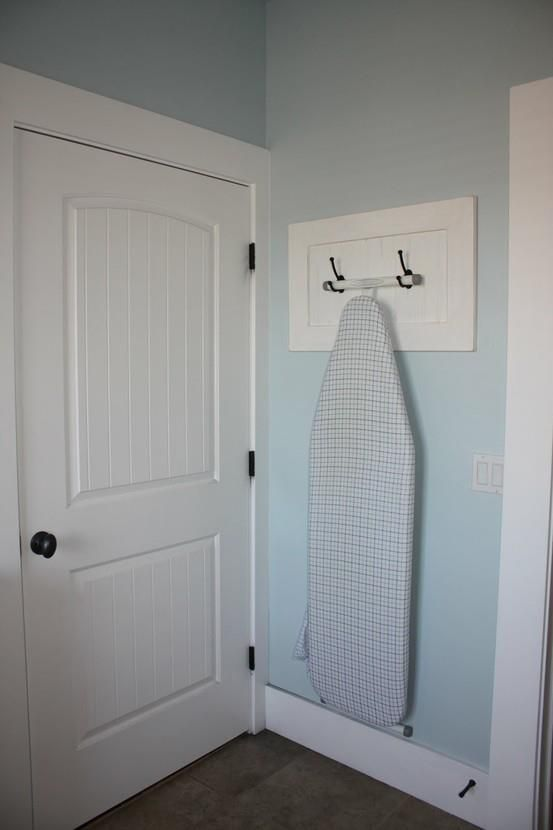 old cabinet door turned into hanger for ironing board