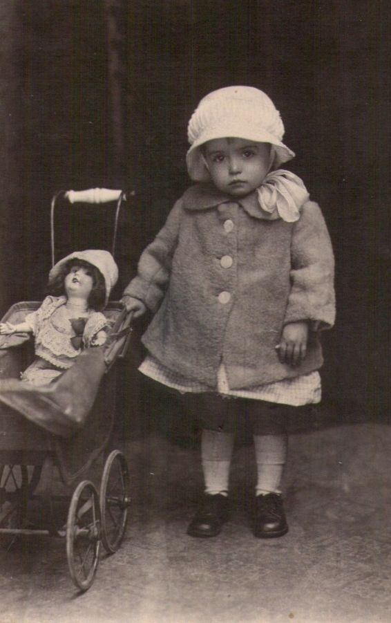 Vintage photo of little girl with her doll in a pram. …