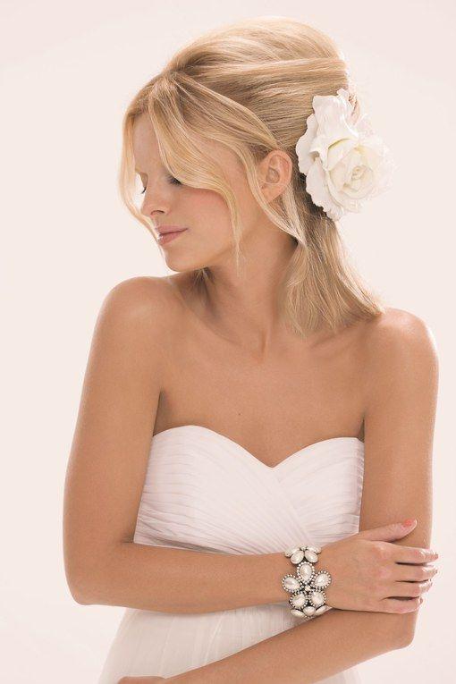 Cette coiffure de mariée, très chic pour cheveux mi-longs, propose une demie queue. Un grand classique indémodable pour votre mariage. On aime : la barrette en fleur qui apporte une touche d'élégance.<br><br><i>© Jacques Dessange