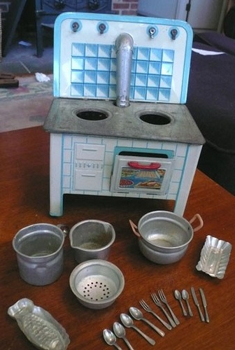 Hated to part with this ! Tin Lithograph Toy Stove with tin cooking ware and flatware .