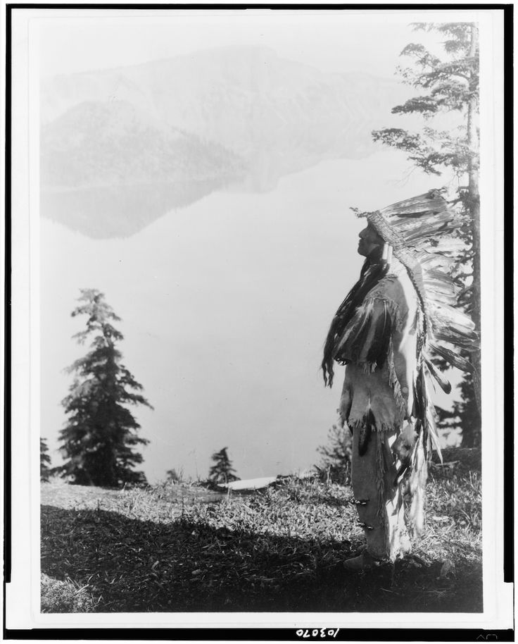Klamath Indian chief in feather headdress standing on mountain overlooking Crater Lake, Oregon. - Curtis - 1923 The Klamath people are a Native American tribe of the Plateau culture area in Southern...