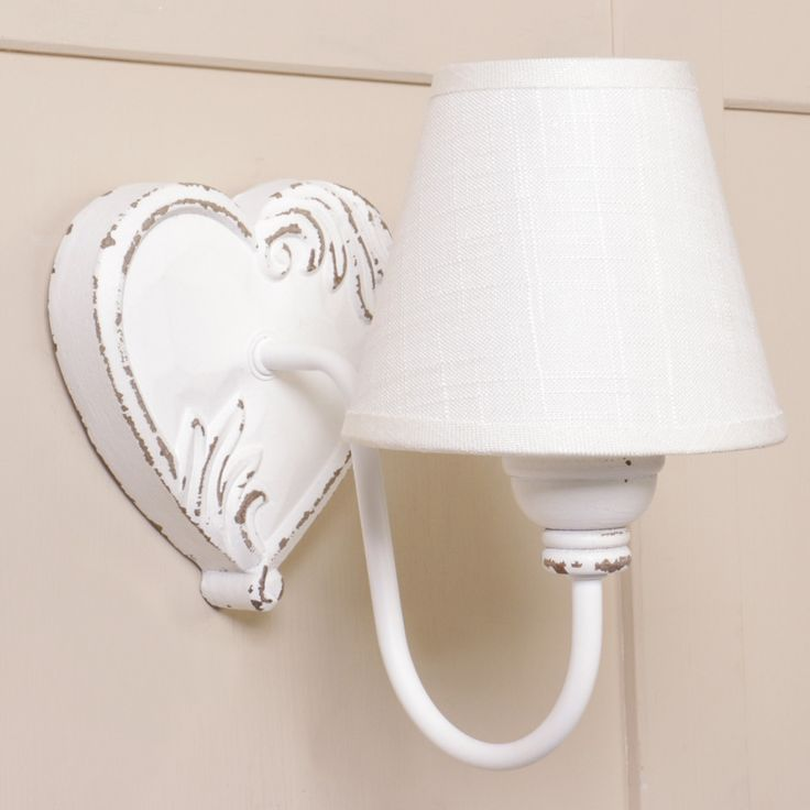 Add decorative lighting to a wall with this wooden heart shape wall light painted in french country