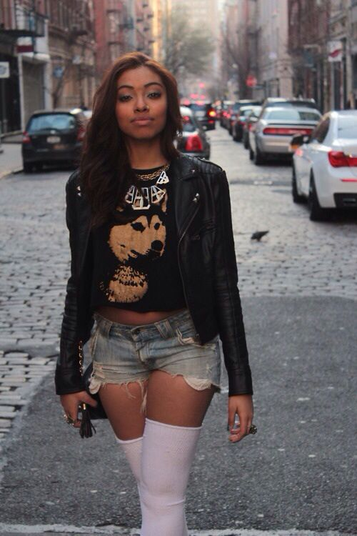 black woman wearing daisy duke shorts cutoff white long stockings leather biker jacket black animal printed tee shirt
