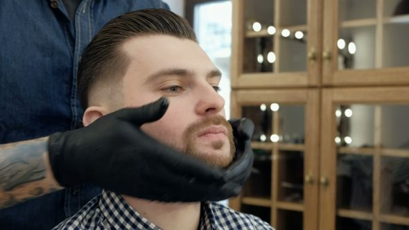 Handsome Bearded Man While Getting Haircut By Hairdresser at the Barbershop