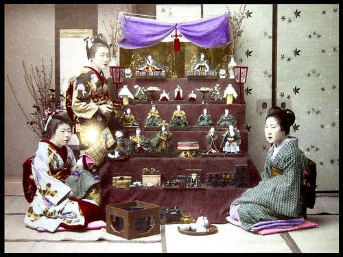 "HINA MATSURI -- ""GIRLS DAY""   Although I do have others, this is one of the best Meiji-era close-content images of the Japanese Doll Festival decorations I have seen during my old-photo-collecting days.  ""The Japanese Doll Festival, or Girls' Day, is held on March 3, the third day of the third month. Platforms with a red hi-mōsen are used to display a set of ornamental dolls (hina-ningyō) representing the Emperor, Empress, attendants, and musicians in traditional court dress of the Heian…"