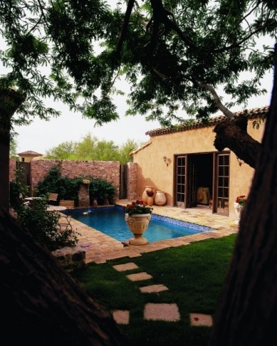 Love the subtle water spout on the far #stone wall, also love the doorway. #pool #Arizona