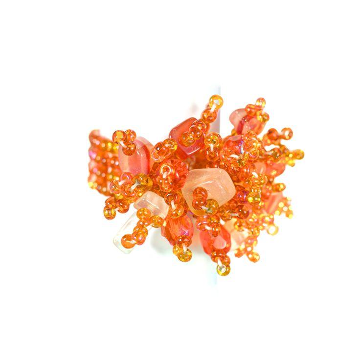 Volcán - en #orange #ring som sticker ut, knuten för hand med hundratals små plastpärlor. På ovansidan exploderar pärlorna i en bukett av olika form och nyans. 90:-