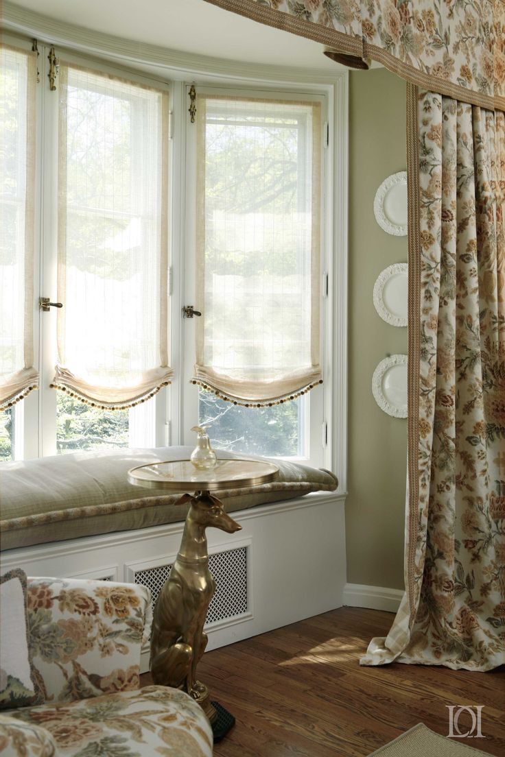 Window Seat With Sheer Roman Shades And Floral Linen
