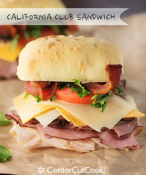 A toasted ciabatta roll with roasted chicken, ham, roast beef, bacon, Swiss & cheddar cheese, guacamole, tomato, and lettuce.