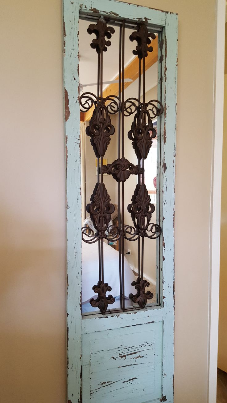 Old gate re-purposed into bedroom wall mirror with character