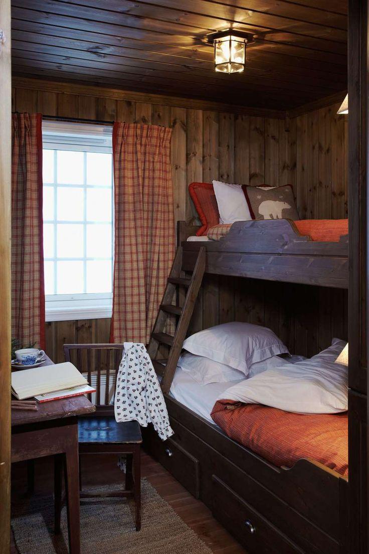 VARME VEGGER: Veggene på dette soverommet er beiset med Jotun interiørbeis i fargen Drivved. Her har de valgt å beise sengen i en mørkere nyanse enn veggen, noe som gir et helhetlig og rolig inntrykk. Rommene på hytta er relativt små, derfor valgte de bort store garderobeskap. Mange kroker og knagger gjør nytten til klesoppheng.   De røde tonene kombinert med de mørke veggene gir det en lun og varm følelse. Hytta er innredet av beboeren Cornelia Thrane Steen, som også er interiørdesigner.