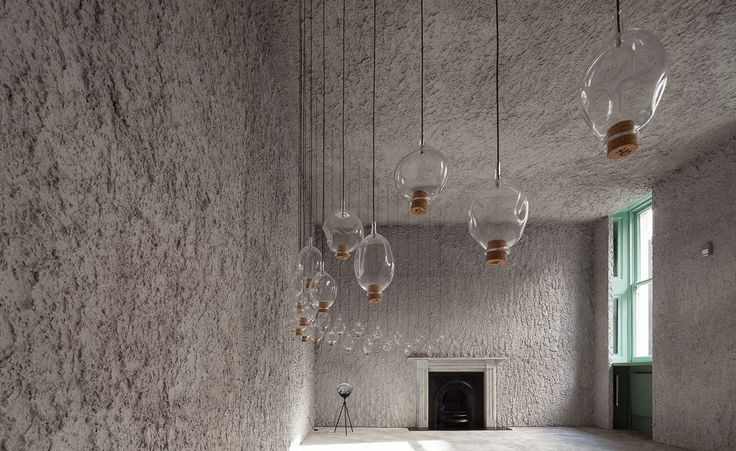 The rough, grey walls are the backdrop for thirty-seven swinging irregular glass forms, each suspended by a black thread in a semi-circle