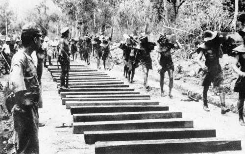 Japanese Forces - Burma Railway. Australian prisoners of war carry heavy wooden sleepers in the construction of the Burma Railway, near Thanbyuzayat, 1943.